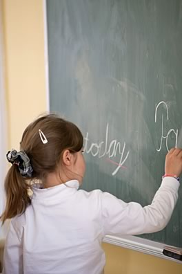 Clanmore elementary student writing on a chalkboard