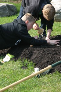 Two Middle School students plant seedlings in their garden as part of their Micro-economy Program.